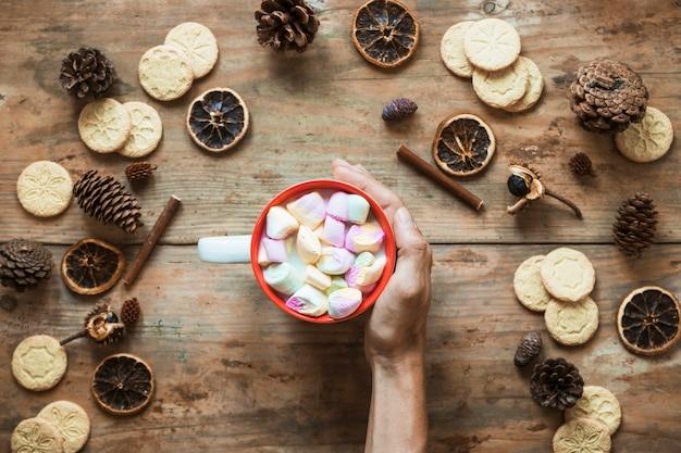 Mão perto de chocolate quente e especiarias