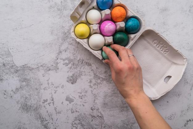 Mão perto de ovos de páscoa brilhantes no recipiente