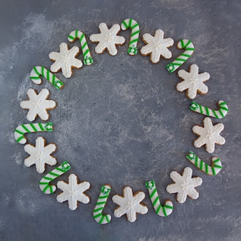 Mão-pintado natal gengibre verde e branco bastão de doces e flocos de neve em um fundo cinza bonito.