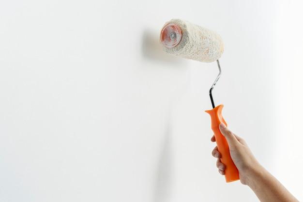 Mão pintando a parede de branco