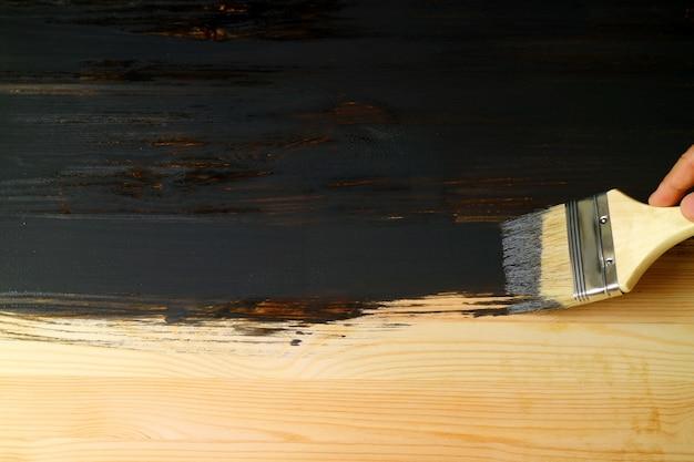 Mão pintando a superfície da prancha de madeira natural com pincel