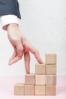 Mão pisando em cubos de madeira