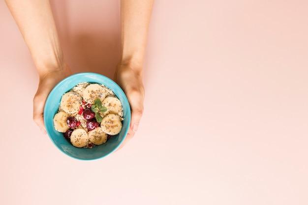 Mão plana leiga segurando a tigela de aveia e frutas com espaço de cópia
