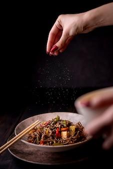 Mão polvilhar sal na tigela de macarrão com legumes