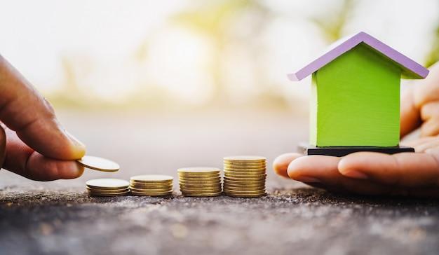 Mão, poupar dinheiro com mini casa e pilha de moedas