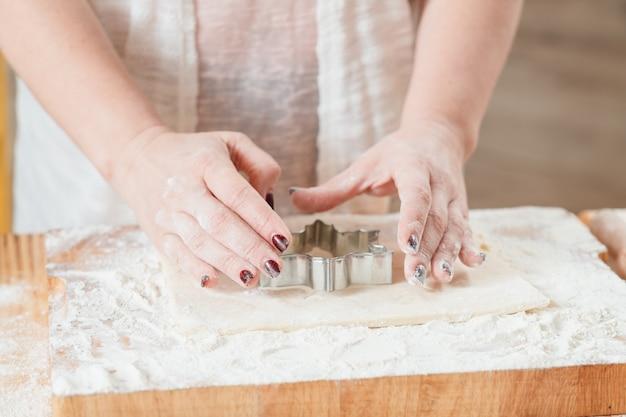 Mão preparando biscoitos com massa na cozinha