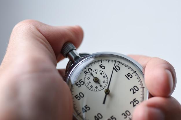 Mão pressiona o botão de início do cronômetro no esporte, medições, metrologia
