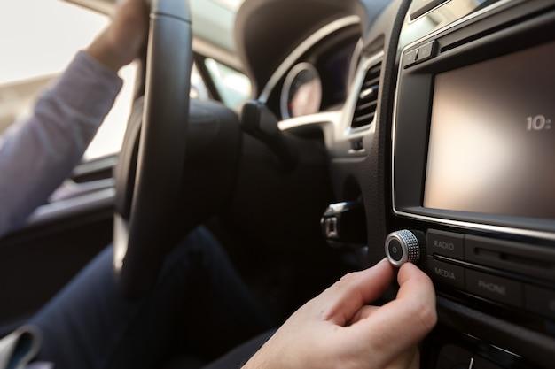 Mão pressionando o botão liga / desliga para ligar o sistema estéreo do carro
