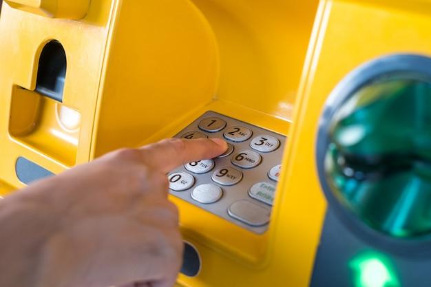 Mão pressionando o código do atm enfoca os números e a área do dedo.