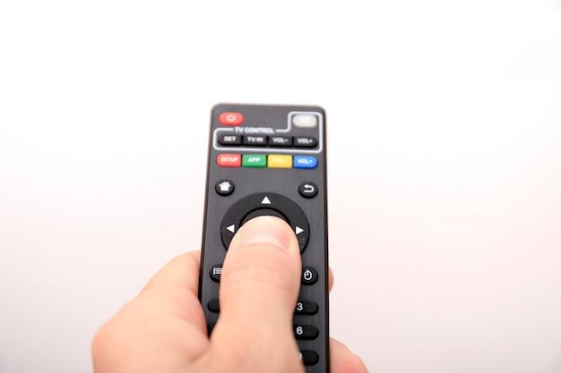 Mão pressionando o controle remoto isolado