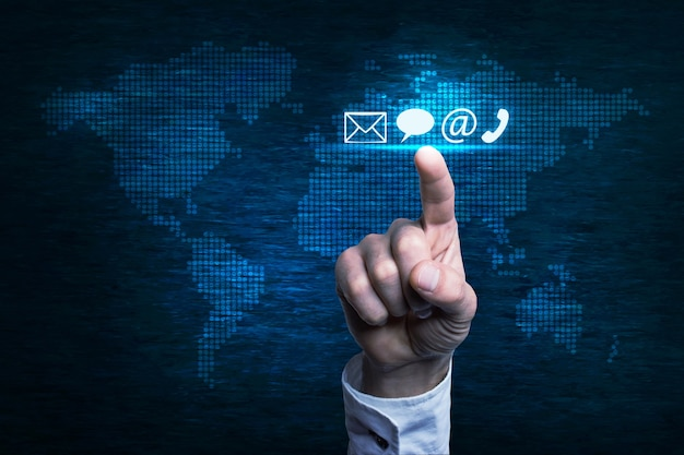 Mão pressionando o ícone de contato sobre o mapa mundial