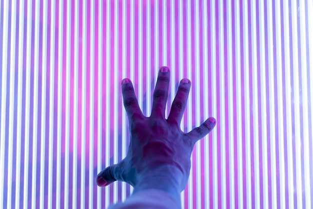 Mão pressionando para abrir a porta futurista de um clube