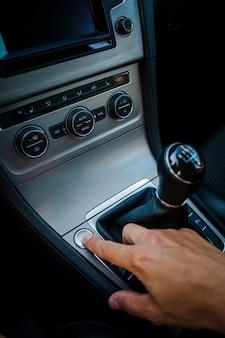 Mão pressionando um botão ao lado da alavanca de câmbio