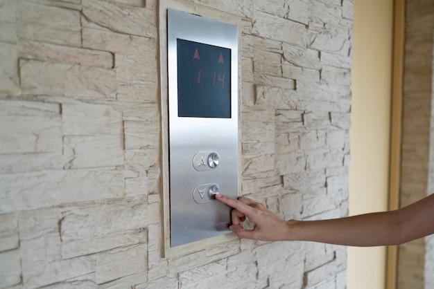 Mão pressione um botão de elevador para andar de baixo nível