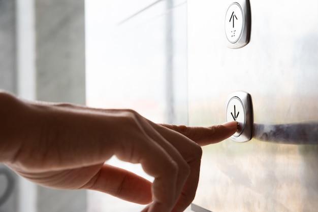 Mão pressione um botão para baixo do elevador dentro do prédio