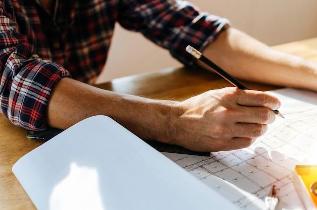 Mão profissional arquiteto, engenheiro ou interior mãos desenhando com blueprint na mesa de trabalho