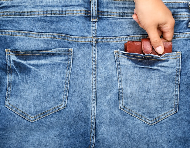 Mão puxa para fora do bolso de trás da calça jeans azul uma bolsa de couro marrom