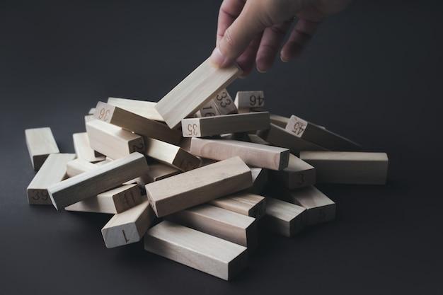 Mão puxa um bloco de madeira de uma pilha dos mesmos blocos. líder, individualidade, melhor trabalhador