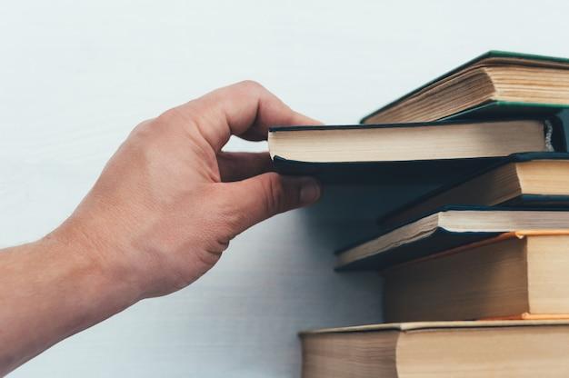 Mão puxa um livro, da estante.