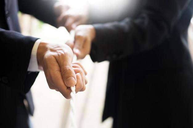 Mão puxando a corda, fundo cinza, conceito de cooperação como elemento do trabalho em equipe.