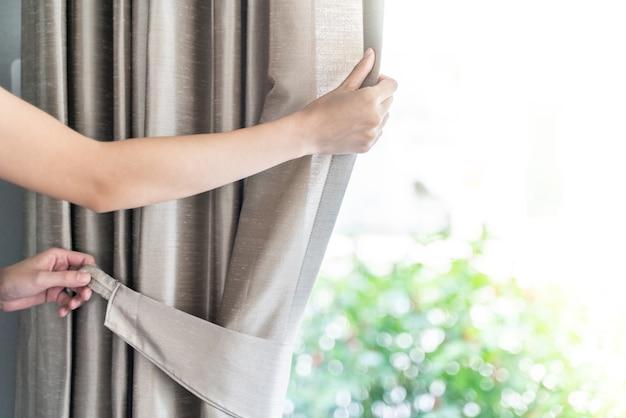 Mão puxando gravata de cortina