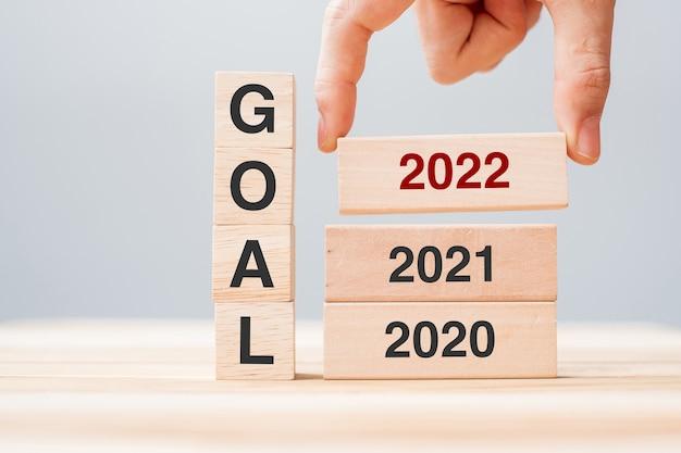 Mão puxando o bloco de 2022 ao longo de 2021 e 2020, edifício de madeira no fundo da mesa. planejamento de negócios, gerenciamento de risco, resolução, estratégia, solução, objetivo, conceito de ano novo e feliz feriado