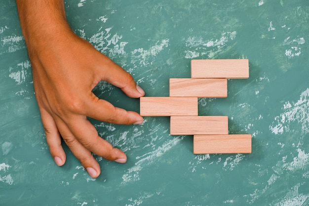 Mão puxando o bloco de madeira.