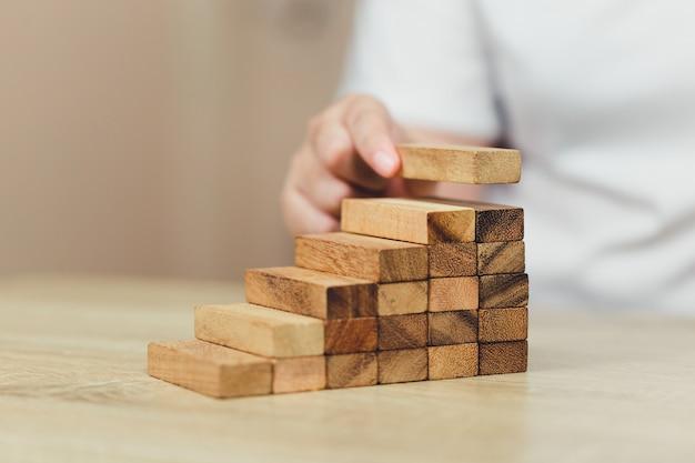 Mão puxando para fora ou colocando o bloco de madeira.