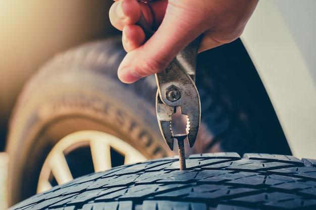 Mão puxando para remover um prego no pneu, pneu furado fixação e reparo o pneu está vazando do tack