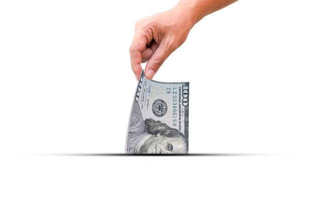 Mão puxe uma metade da nota de dólar dos eua. o dólar americano é uma moeda mundial e popular para troca com outras moedas.