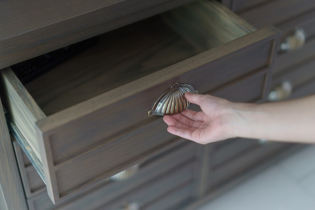 Mão que abre as gavetas de madeira marrons dos arquivos.