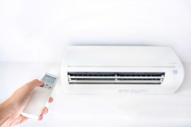 Mão que ajusta a temperatura do ar condicionado por controle remoto dentro da sala.