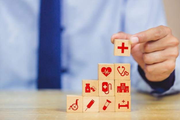 Mão que arranja o bloco de madeira que empilha com os cuidados médicos do ícone médicos.