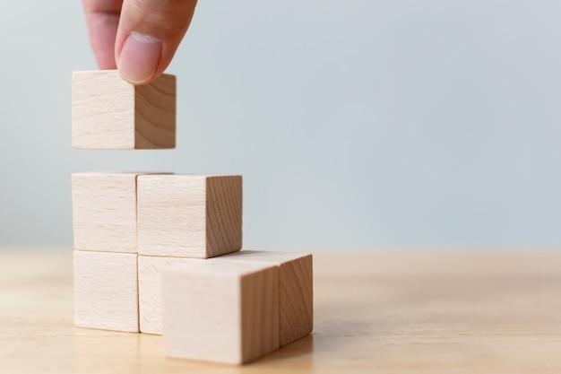 Mão que arranja o bloco de madeira que empilha como a escada da etapa na tabela de madeira. conceito de negócio para o processo de sucesso de crescimento.