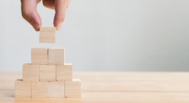 Mão que arruma o bloco de madeira que empilha como a escada da etapa. conceito de negócio para o processo de sucesso de crescimento