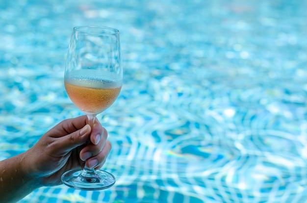 Mão que brinda com uns vidros do vinho de rosa na piscina.