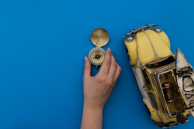 Mão que coloca bússola e carro de brinquedo