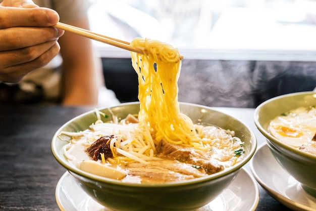 Mão que comprime o macarronete com vapor no caldo dos ramen com pasta picante do feijão (miso ramen).