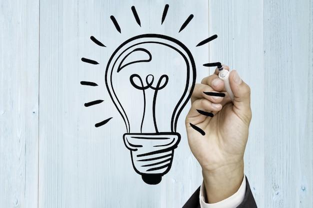 Mão que desenha uma lâmpada