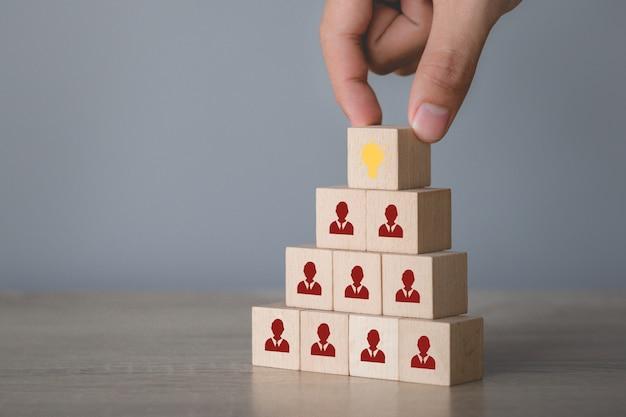 Mão que escolhe cubo de madeira com ícone da lâmpada e símbolo humano.