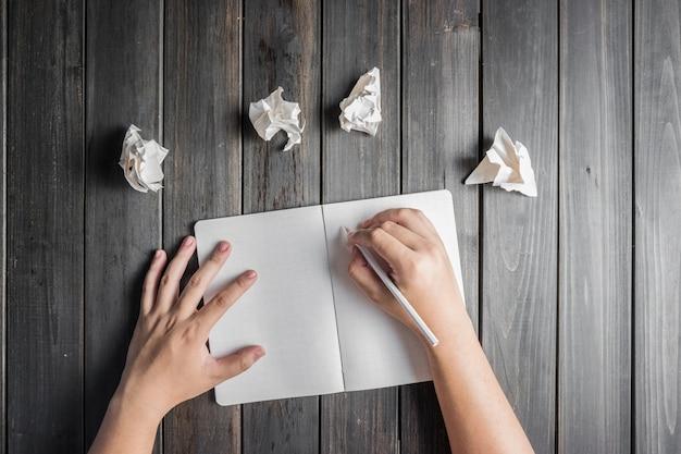 Mão que escreve ao lado de algumas bolas de papel