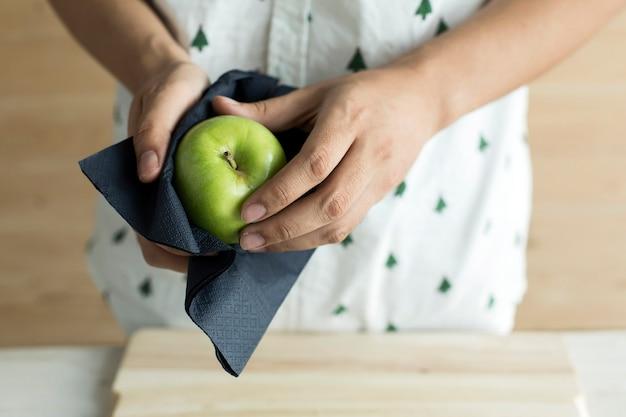 Mão que limpa a maçã verde