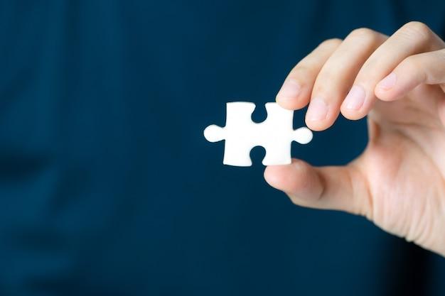 Mão que mostra a parte vazia do enigma de serra de vaivém para exprimir o fraseio. conceito de apresentação do negócio.