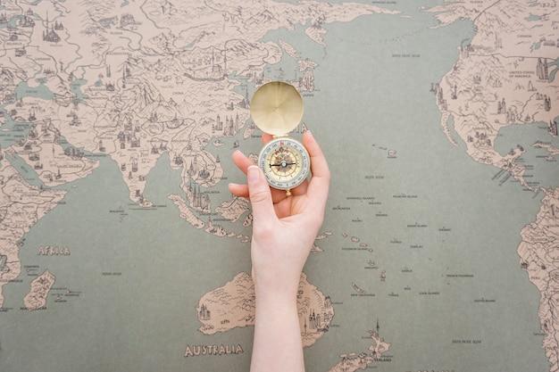 Mão que mostra um compasso com fundo mapa do mundo