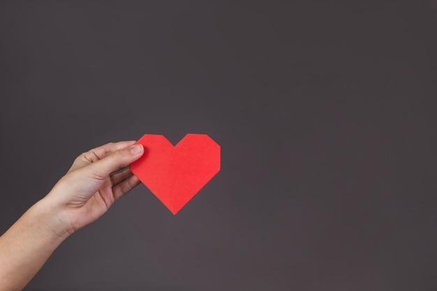 Mão que prende um coração de papel