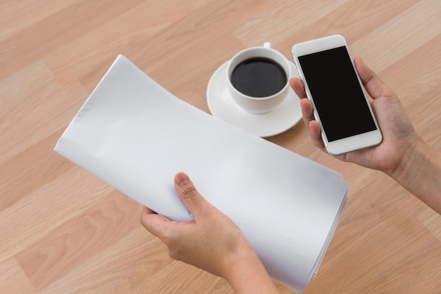Mão que prende uma folha de papel, um celular e um café na mesa