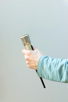 Mão que segura o microfone