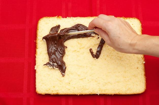 Mão recheio de bolo caseiro com ganache de chocolate isolado na vista superior de fundo vermelho