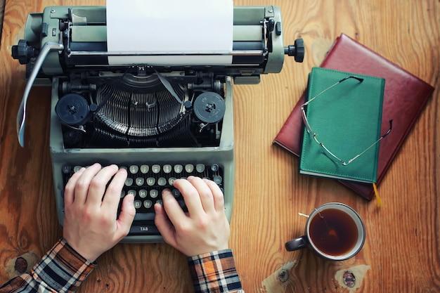 Mão retrô de máquina de escrever na mesa de madeira
