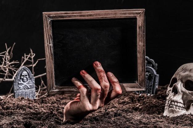 Mão, saliente, de, sepultura, segurando, quadro-negro